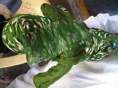 El hilo verde teñido con la técnica Ikat está listo para tejer. Aquí se lo ve junto a una muestra de la tela que se le envió al proveedor para reproducir.