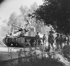 A Sherman tank and infantry advance