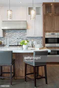 Two-tone cabinets might be all the rage, but mixed materials also keep things interesting. White countertops on stained cabinetry add to the appeal. Kitchen Pendant Lighting, Kitchen Pendants, Pendant Lights, White Kitchen Island, Kitchen Islands, White Countertops, Home Buying, Home Renovation, Home Kitchens