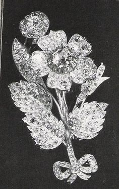 The Queen`s antique diamond set design of a wild rose with three leaves on a sprig, tied with a small bow at the base. This brooch was a gift to Princess Elizabeth from Messrs John Brown (Shipping) for launching the HMS Vanguard in 1944.