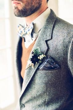 bow tie. tweed jacket, pocket square, and lapel flower