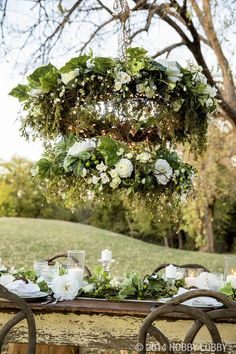 This two-tiered DIY chandelier is made from grapevine wreaths, white blooms, greenery and twinkle lights. We'll show you how!