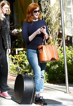 Christina Hendricks sported jeans, a navy sweater, a leather tote and demure cat-eye sunnies for a casually chic look!