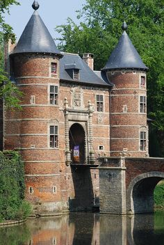 Château de Grand-Bigard, Belgique. L'origine du château remonte au début du XIIe siècle. On y accède par un pont, commandé par deux magots héraldiques du XVIIe siècle, puis un pont-levis qui débouche sur le châtelet d'entrée dont la partie centrale date du XIVe siècle. Le château, érigé au XVIIe siècle, constitue un spécimen remarquable de la Renaissance flamande, et se compose d'un long corps de logis à un étage. Le donjon, à gauche du châtelet, érigé vers 1347, culmine à plus de 30 m.