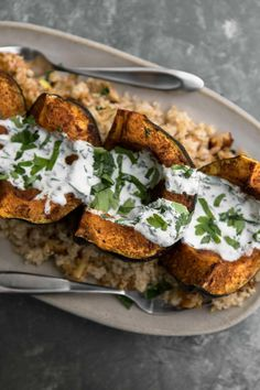 Roasted harissa acorn squash served with easy onion bulgur and topped with a mix of cilantro/parsley, yogurt, and lemon juice. A perfect vegetarian side dish or main dish.