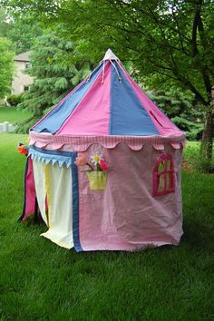 Round circus-style playhouse.  I like the hanging flower pots with removable daisies.  A tent-top or A-frame playhouse makes the most sense to me, because it gives some extra room for bigger kids.  The card table flat-top playhouses look pretty small inside.