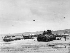 Wrecked vehicles and equipment on Dog beach, OMAHA Area, after the initial assault, 6th June 1944. The M4 Sherman tank in the foreground is 'Ceaseless', 'C' company, 743rd Tank Battalion.
