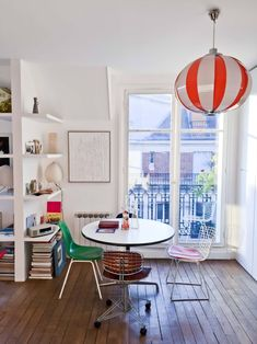 """A space-saving circular George Nelson table is surrounded by a sampling of Marie's chair collection, including a green Eames chair (""""from a cafeteria in the Pigalle that closed""""), a steel-and-leather Renzo Piano library chair salvaged from the Pompidou, and aBertoia Side Chair with """"a very vintage orange leather cover."""""""