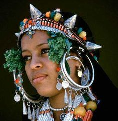 The two pictures below show examples of the exuberant berber jewelry from northern Sahara. Chains, little bells, sleigh bells, coins, beads and huge earrings, are all present around the women heads.