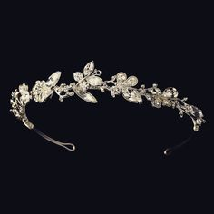 "This charming tiara features a subtle butterfly design, glittering with rhinestones and silver details. The decorated portion of the band measures 9"" wide and 1"" tall, and the piece ends in loops that"