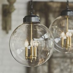 Clear Glass Globe Hanging Lantern- shades of Light. I like the brass candle holders with/in the bronze lantern. Also- 3 lights!