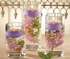 Arranjo com flores, velas e copos de vidro