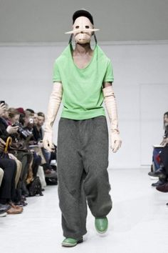 Walter Van Beirendonck Paris A/W 2012 Garment being held up by the hat similar to the way a puppet is help by strings. Shape of garment determined by accessories not necessarily the shape of the body it is on. Interesting when paired with the plastic mask and gloves covering and changing the impression of the body.
