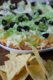 Mexican Layered Dip ~ Mexican appetizer for snacking, parties, or game days. Layers of refried beans, sour cream, guacamole, tomatoes, cheddar cheese, onions and olives make this familiar dip a sure winner