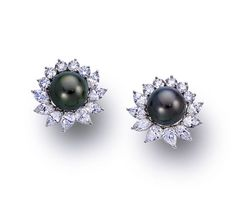 A pair of South Sea cultured pearl and diamond earclips, Tiffany & Co.  each centering a dark gray South Sea cultured pearl, measuring approximately 11.50 to 12.00mm., surrounded by pear-shaped, marquise and round brilliant-cut diamonds; signed Tiffany & Co.; estimated total diamond weight: 6.40 carats; mounted in platinum; diameter: 1in.