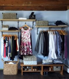 A closet is made where there is none against a bedroom wall using brackets, shelves, baskets and pipe.