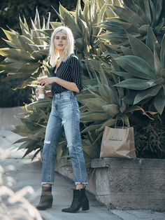 Rima stuns with bleach blonde hair, a striped shirt, cropped high-waisted jeans and ankle boots.