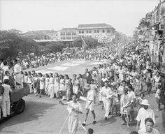 The people of Singapore celebrate the Japanese surrender with a parade.  1945