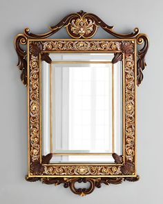 """Handcrafted wall mirror. Mahogany frame with hand-carved, cast pewter embellishments with an 18-kt. matte gold and medium brown antiqued finish. Hand enameled and hand set with Swarovski crystals. 36"""""""