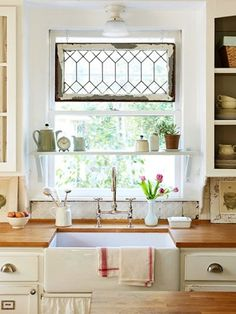 farmhouse sink, glass cabinet doors, old window panel at the top and the shelf across the window, the old tin tile back splash, need I go on??