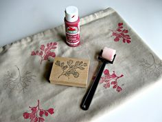 With a rubber stamp and acrylic paint, you can make your own patterned material. Just add heat after to seal the deal (and wait about a week before washing).