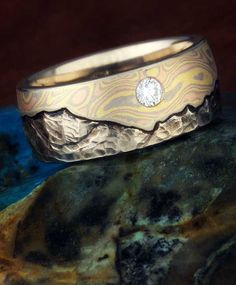 This Mountain Mokume Wedding Band was done with a Trigold Mokume sky and a round white diamond accent stone. Let us know what mountain range is your favorite and we will hand-carve it into your band. Also, select from our 7 mokume gane flavors....