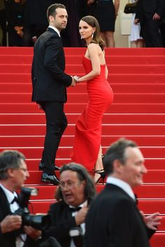 Natalie Portman is a red Dior gown at Cannes with her husband Benjamin Millepied