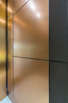 LEVELe-105 Elevator Interior with panels in Fused Bronze with Linen finish, Bonded Bronze with Dark Patina and Charleston pattern at…