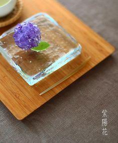 . Today I made japanese confection #nerikiri which is hydrangea shaped 自由が丘の駅近くの「大文字」(だったかな?)という老舗の和菓子屋さんで、 真紫の紫陽花の上生菓子を見かけました。 . 餡?が真紫で。周りにつけてある錦玉が透明。 . 淡い色の紫陽花ばかり作っていたので それがとっても新鮮に映って,,,,,,,. . 今日は真紫バージョンの紫陽花をおやつに作ってみました。 . . 真紫と言っても、白餡をマーブル模様の紫の練り切りで包餡してから、透明の、ランダムにみじん切りにした均一に玉をまとわせたので、 濃い紫の部分と薄い紫の部分が出来て キララ綺麗〜✨✨✨ . . . .お問い合わせの多いガラスの器は、5月半ば、伊勢丹新宿店で購入しました。作家さんものらしくサインがしてあって、最初が「T」で、最後が「i」と書いてあります。 . #wagashi#上生...