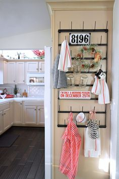 "A wall mount drying rack is the perfect place to display fun kitchen decor like a vintage apron, mason jars, a snowman mug, enamel wear filled with mini candy canes and the wreath, tea towels and red glitter ""I'm only a Christmas person on December 25th"" wood sign from HomeGoods - See more of this vintage cottage holiday home tour at foxhollowcottage.com sponsored pin"