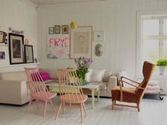 love those Windsor chairs!   An all-white living room set off by touches of pink—two Windsor chairs painted in different pale hues, hot pink pillows and artwork, and light-pink blankets.
