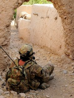 An Australian soldier from Mentoring Task Force Three provides security while Afghan National Army soldiers conduct compound searches during a clearing patrol of the Tangi Valley, southern Afghanistan.