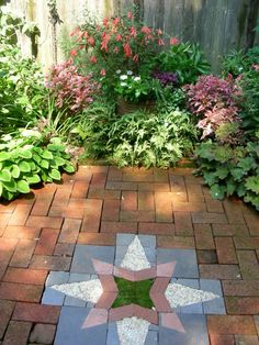 "Here's the experimental mosaic of tile, embedded pea gravel and moss in the center of the garden's octagonal brick ""entry foyer"" space which you walk through before......."