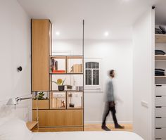 Adrian Elizalde and Clara Ocaña broke down walls to create a open-plan layout for this apartment in Barcelona, and lined its rooms in warm-toned wood.