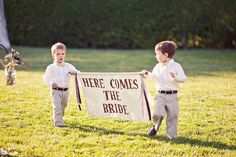 """our ring bearers carrying """"here comes the bride"""" sign"""