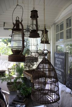 Hanging bird cages and lanterns above an outdoor table.