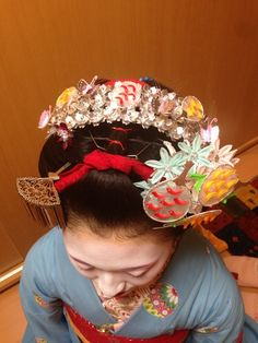 unior maiko from Kyoto keep their hair styled in wareshinobu hairstyle for the Gion Festival but decorate it with elaborate silver crowns and special flowers-and-fans kanzashi. The design is changed every year!