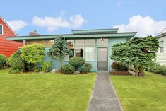 Adorable turquoise mid century modern house with a lot of Asian influence. Great plantings, too.