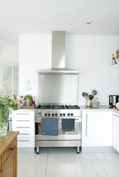 i love this kitchen. gleaming stainless steel, lots of soothing smooth white surfaces, plenty of natural light, and sleek metal cabinet pulls. plus a little peek of nice natural wood and greenery to warm it up. Kitchen Interior, Kitchen Inspirations, Small Kitchen, Kitchen Designs Layout, Kitchen Decor, New Kitchen, Home Kitchens, Rustic Kitchen, Kitchen Renovation