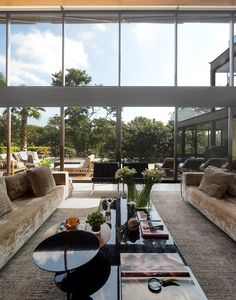Home Decorations: Inspiring Tropical Style Design For Double Height Living Room Near Glass Wall Presenting Refreshing Greens Outside from Bright Venue in Lavish Elements
