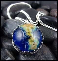 I made this glass cabochon to look like the Earth. I set it into a sterling silver bezel style pendant, which I also created. The bezel on the side looks like people holding hands and holding the Earth...I love it and I kept it in my own personal collection