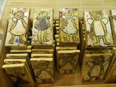 #Kids project, self portraits as angels. Carved with pencil and painted with underglaze.