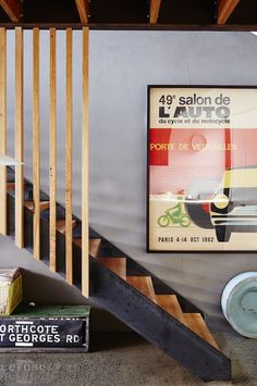 Stairs made from recycled Australian hardwood, grey rendered wall. Vintage French poster from Gallery Montmartre. Old tram sign found in a junk shop in Collingwood. Production – Lucy Feagins / The Design Files.