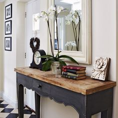 Perfect monochrome style - black and white chequerboard floor tiles, rustic black console table and classic accessories
