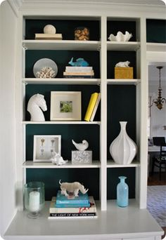 It's OK to be Single. Smaller cubbies look simply perfect with a textured or sculptural object placed all by itself. Notice the use of a single vase or shell in the smaller spaces of John & Sherry's bookcase, and the fantastic contrast with bold blue and crisp white.