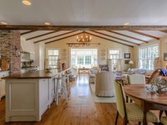 This charming Sag Harbor open kitchen and living area has white cabinets, large plank wood flooring, exposed wood vaulted ceiling and adorable checkered upholstered seating.
