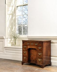A George II crossbanded and featherbanded kneehole desk