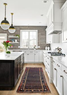 White floating shelves are mounted to a gray oak plank backsplash beside a window positioned above a sink with a pull out faucet.