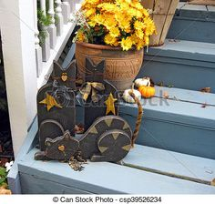 Wooden black cats and a pot of mums on the front porch steps welcome the Fall season.