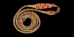 PRE-COLUMBIAN EMBROIDED TEXTILE SLINGSHOT Inca Empire, 1438-1532 AD  A braided textile band with tapering round-section ends and flat-section centre in red, cream and brown wool. 93 grams, 290 cm